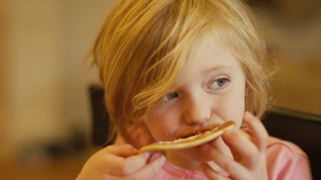 Una-niña-comiendo-un-panqueque-con-las-manos-de-cerca-a-cámara-lenta