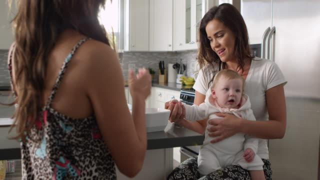 Female-couple-in-the-kitchen-with-their-baby-girl-on-knee-shot-on-R3D