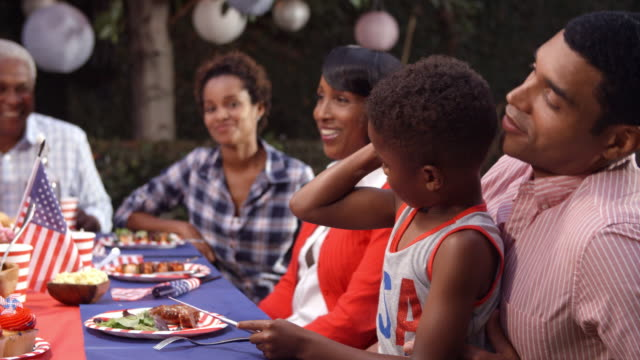 Young-boy-on-dad's-knee-at-family-barbecue-flexing-muscle