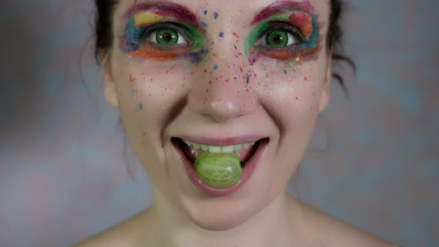 4k-Shot-of-a-Woman-with-Multicoloured-Make-up-Eating-Gooseberry