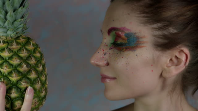 4k-Shot-of-a-Woman-with-Multicoloured-Make-up-with-Pineapple