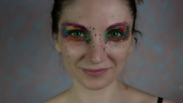 4k-Shot-of-a-Woman-with-Multicoloured-Make-up-with-Melon
