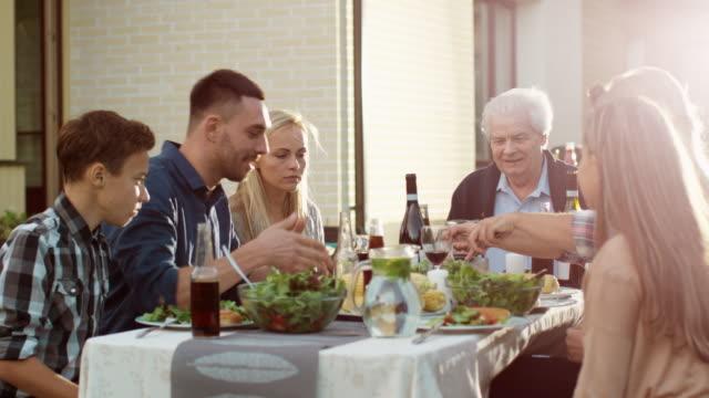 Grupo-de-personas-de-raza-mixta-teniendo-diversión-comunicación-y-comer-en-la-cena-al-aire-libre-de-la-familia