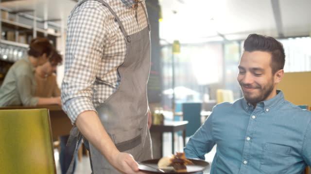 Waiter-bringing-Ice-Cream-Dessert-for-Handsome-Young-Man-at-Restaurant-