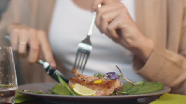 Attractive-Young-Woman-Enjoying-Fish-Steak-at-Luxury-Restaurant