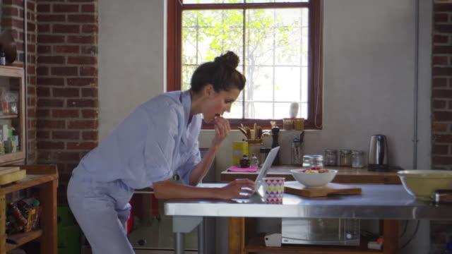 Young-woman-in-pyjamas-using-laptop-in-kitchen-shot-on-R3D