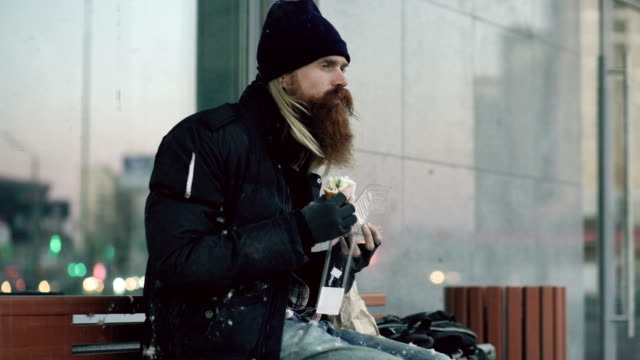 Homeless-young-man-eating-sandwich-on-bench-at-city-street-in-evening