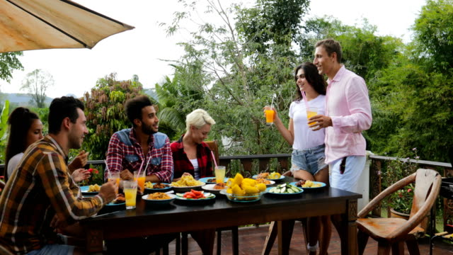 Couple-Telling-Toast-Standing-Up-People-Eating-On-Terrace-Young-Friends-Sitting-At-Table-Outdoors-Communication
