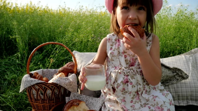 Weekend-at-picnic-Girl-on-flower-meadow-with-pastries-and-milk-Happy-joyful-child-Lovely-girl-on-flower-meadow-with-basket