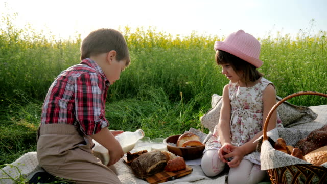 Friends-on-green-lawn-kids-at-picnic-Boy-and-girl-with-food-on-nature-Happy-children-in-fresh-air-Boy-pours-milk-into-glass-for-girl