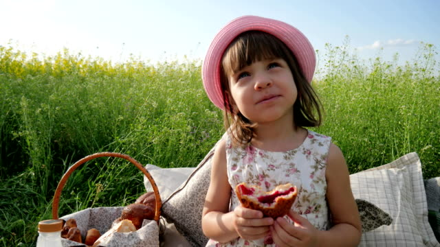 female-child-in-panama-with-bun-on-nature-Weekend-at-picnic-Girl-on-flower-meadow-with-pastries-and-milk-Happy-joyful-child