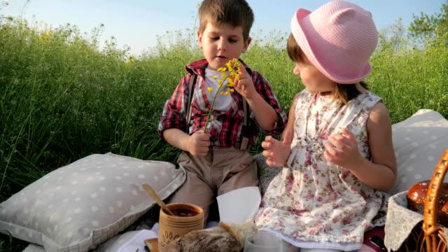 Familia-al-aire-libre-muchacho-con-campos-de-flores-en-la-mano-está-mirando-a-la-chica-hermosa-dos-hijos-adorables-muchacho-está-mirando-a-la-hermosa-chica