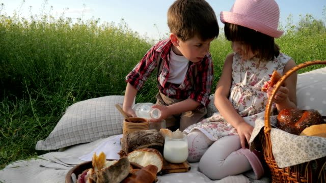 Children-at-picnic-family-is-resting-in-nature-kid-drinking-milk-happy-girl-eating-bakery-croissant-brother-and-sister