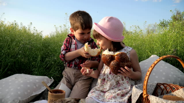 boy-feeds-girl-with-bakery-product-Cute-little-kids-sharing-bread-Products-in-picnic-baske-Children-having-fun-in-fresh-air