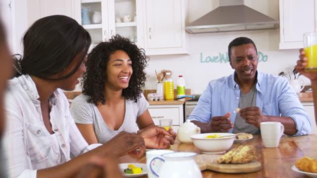 Familia-con-hijos-adolescentes-que-desayunan-en-la-cocina