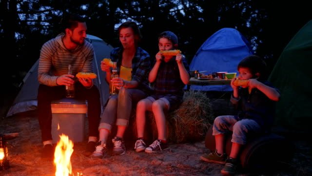 woman-and-male-drink-beer-and-eat-up-fresh-yellow-maize-from-out-fire-during-summer-holidays-family-enjoying-corn-with-salt