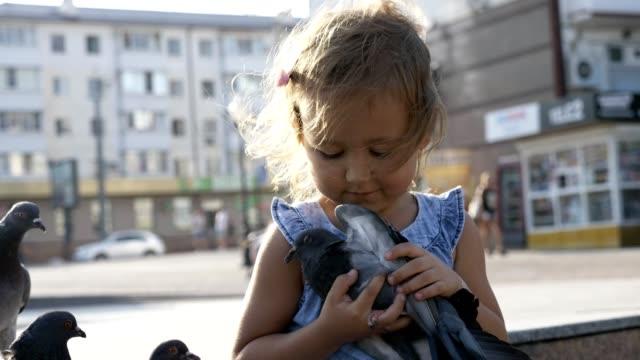 Kleine-süße-Mädchen-im-Park-am-Sommer-Tag-4K-Slow-Motion-Straße-Tauben-füttern
