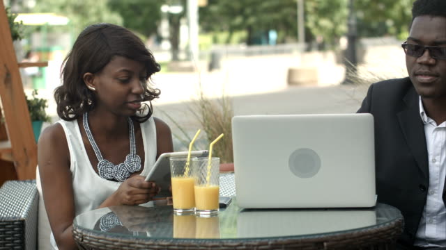 Afro-american-business-man-and-woman-working-together-in-modern-cafe-having-phone-calls-using-laptop-and-digital-tablet