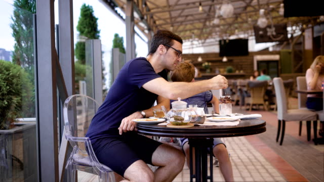 Handsome-man-in-casual-blue-shirt-and-breeches-sitting-in-restaurant-with-son-and-people-in-the-background-Young-father-eating-dessert-of-child-with-long-teaspoon-Little-boy-talking-to-male-parent