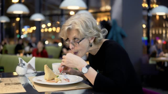 A-middle-aged-woman-eats-dessert-in-a-cafe-