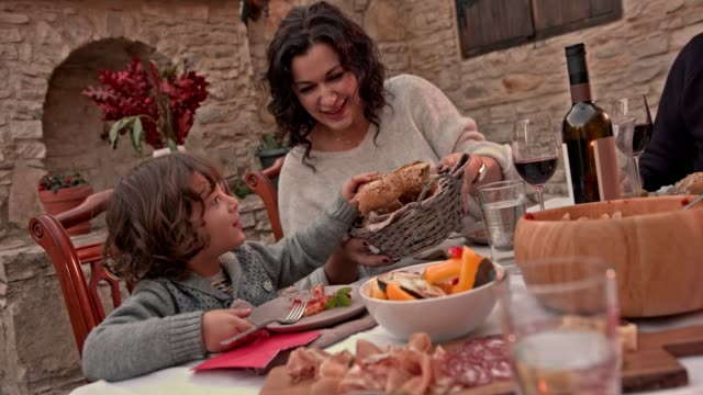 Grandmother-and-grandson-having-lunch-with-family-at-village-house