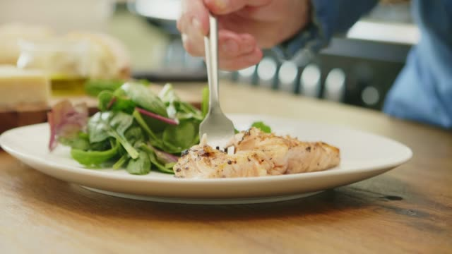 Man-Having-Grilled-Fish-Served-With-Salad-At-Home