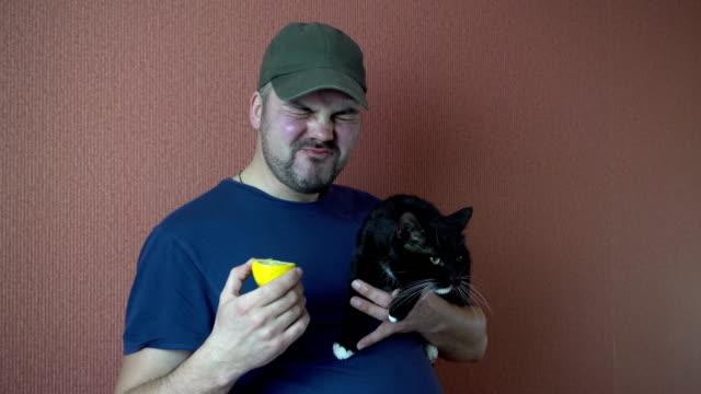 Un-hombre-con-un-gato-en-la-mano-comiendo-un-limón