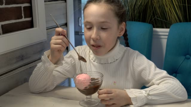 A-little-girl-with-freckles-on-her-face-sitting-in-a-cafe-and-eating-ice-cream-