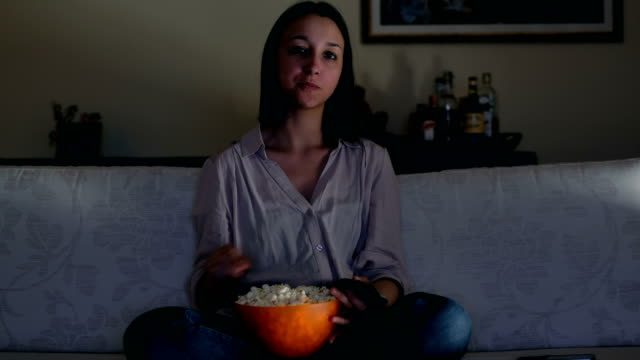Young-woman-watching-her-preferred-show-on-tv