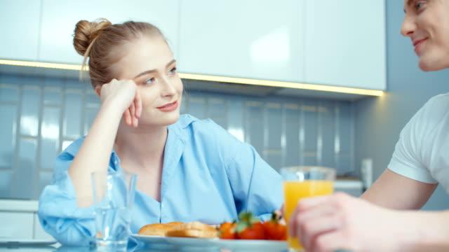Retrato-de-feliz-joven-pareja-durante-el-desayuno-en-casa-