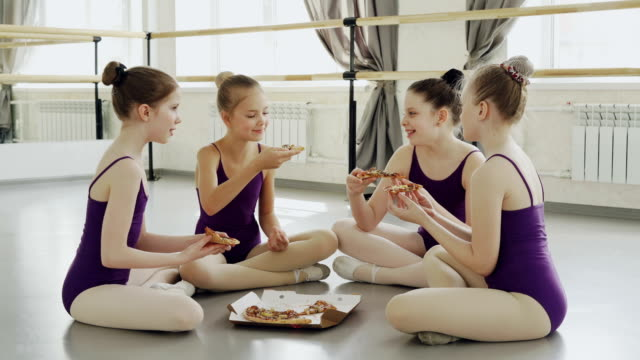 Happy-girls-in-bright-leotards-are-eating-pizza-and-talking-while-sitting-on-floor-of-ballet-studio-together-Tasty-food-communication-and-children-concept-