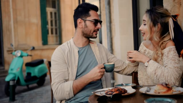 Young-friends-having-breakfast-and-drinking-coffee-at-traditional-cafe