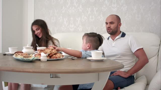 Familia-feliz-jugando-juntos-desayunando-en-la-mesa-del-restaurante