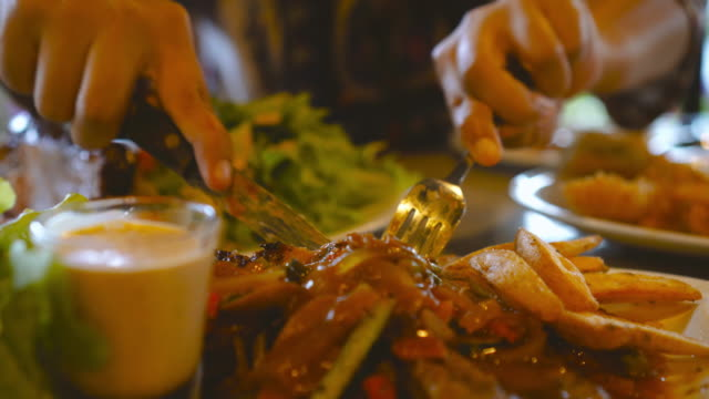 Steak-cut-with-knife-on-plate-by-asian-woman-in-luxury-restaurant-Healthy-eating-and-diet-concept-