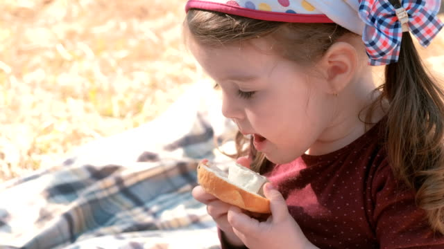 Little-cute-girl-eats-sandwich-with-bread-and-processed-cheese-Family-picnic-Licks-her-dirty-fingers-
