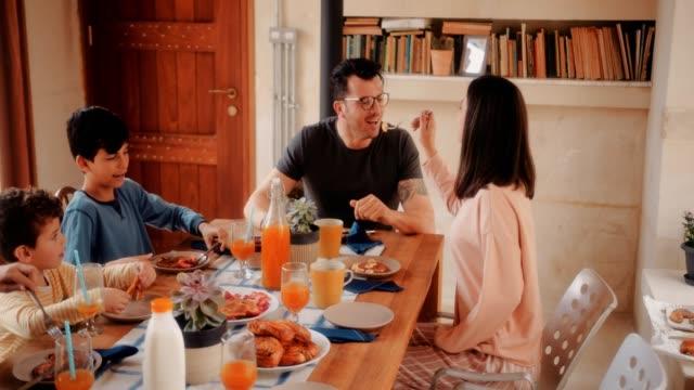 Feliz-esposa-esposo-panqueques-de-alimentación-durante-el-desayuno-con-la-familia