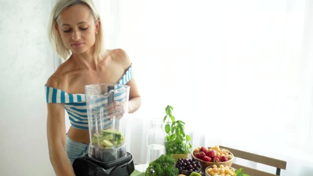 Woman-making-green-vegetable-smoothie-with-blender-Healthy-eating-lifestyle
