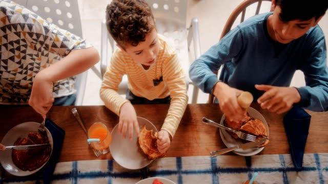 Niños-sentados-a-la-mesa-de-la-cocina-y-desayunando-juntos