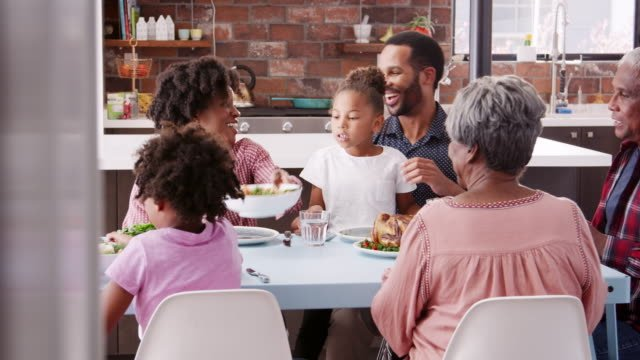 Multi-generation-family-saying-grace-before-enjoying-meal-at-home-together---shot-in-slow-motion
