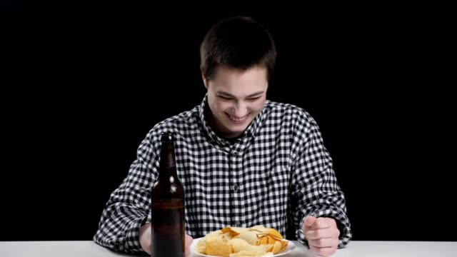 Young-mannish-girl-finished-eating-chips-and-drinking-beer-smiling-laughing-diet-conception-black-background