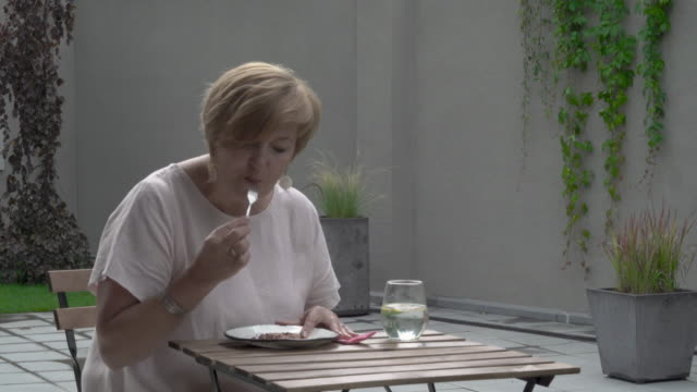 An-aged-woman-finishes-eating-a-cake-She-is-sitting-outside-in-the-terrace-She-wipes-her-lips-and-drinks-some-water-afterwards
