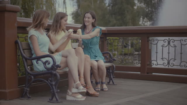 Three-beautiful-girlfriends-eating-ice-cream-on-bench