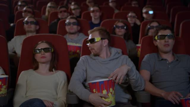 Jóvenes-sentados-en-la-sala-de-cine-viendo-películas-en-3D-y-comer-palomitas-de-maíz