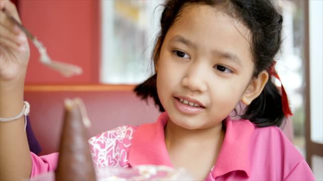 Movimiento-lento-niña-asiática-come-helado-con-felicidad