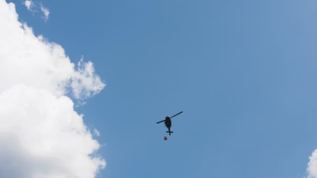 HALLSTATT-AUSTRIA---22-de-agosto-de-2018-helicóptero-toma-agua-en-el-lago-para-combatir-el-incendio-en-las-montañas