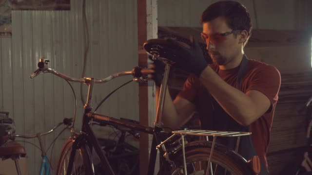 theme-small-business-bike-repair-A-young-Caucasian-brunette-man-wearing-safety-goggles-gloves-and-an-apron-uses-a-hand-tool-to-repair-and-adjust-the-bike-in-the-workshop-garage