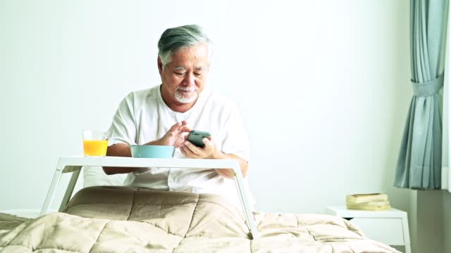 Senior-man-using-mobile-to-call-nurse-to-collect-his-finished-breakfast-Beautiful-asian-woman-with-old-asian-man-with-white-beard-in-bed-Senior-home-service-concept-
