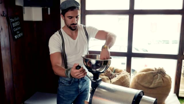Man-operating-a-coffee-beans-roasting-machine-by-the-window-on-a-autumn-day-Pan-shoot