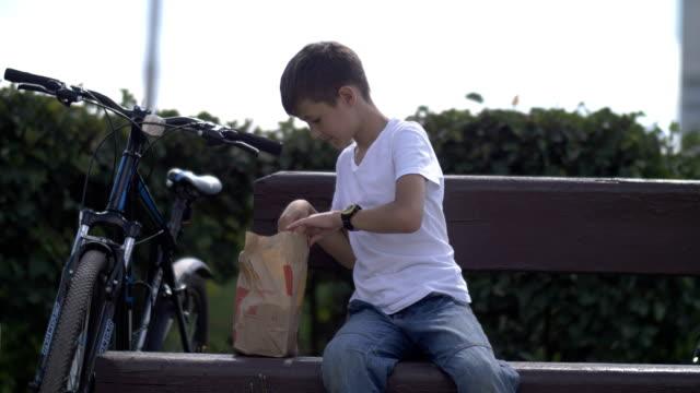Junge-sitzt-auf-einer-Bank-in-einem-Park-öffnet-ein-Paket-und-nimmt-heraus-essen-ein-Picknick