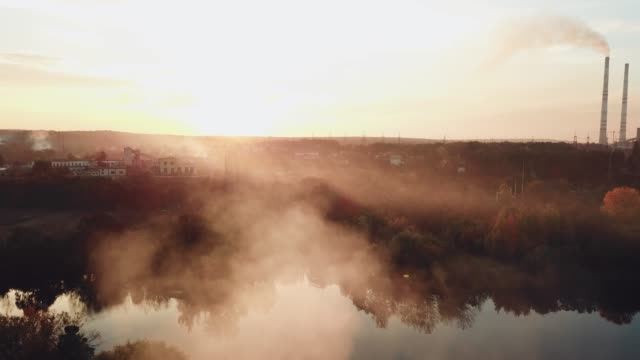 smoke-from-the-fire-are-spreading-over-the-river-at-sunset-on-the-background-of-a-power-station-with-two-pipes-